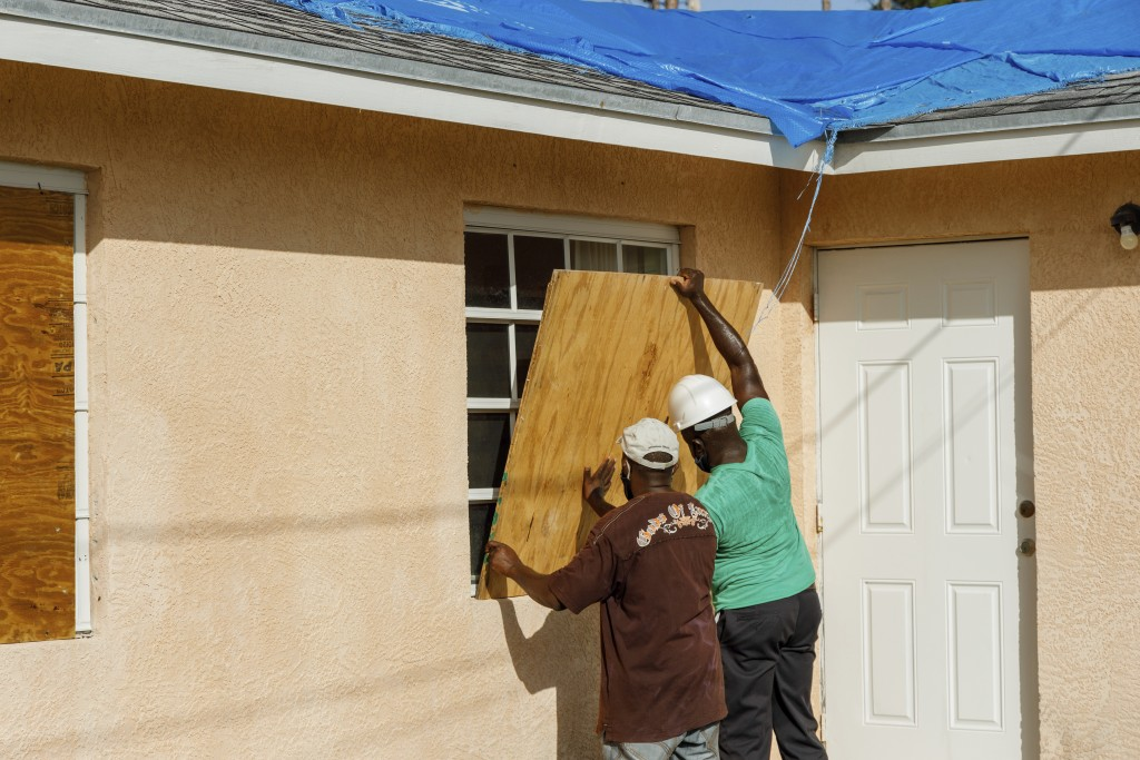 Residents cover a window with plywood in preparation for the arrival of Hurricane Isaias, in the Heritage neighborhood of Freeport, Grand Bahama, Baha...