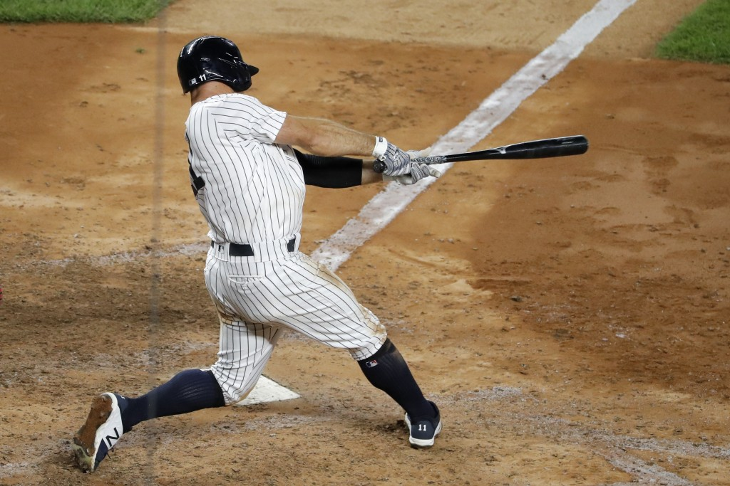 New York Yankees' Brett Gardner follows through on a two run home run during the eighth inning of the baseball game against the Boston Red Sox at Yank...