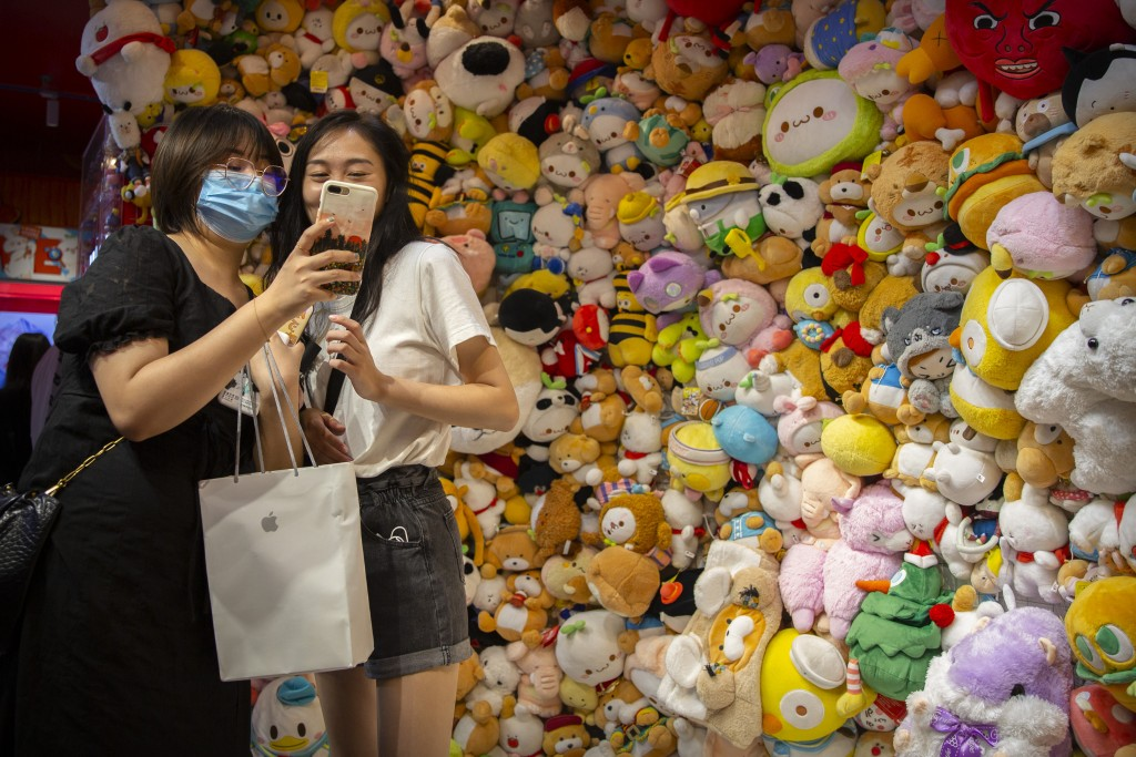A woman wearing a face mask to protect against the coronavirus poses for a selfie in front of a wall of stuffed animals at an arcade in Beijing, Satur...