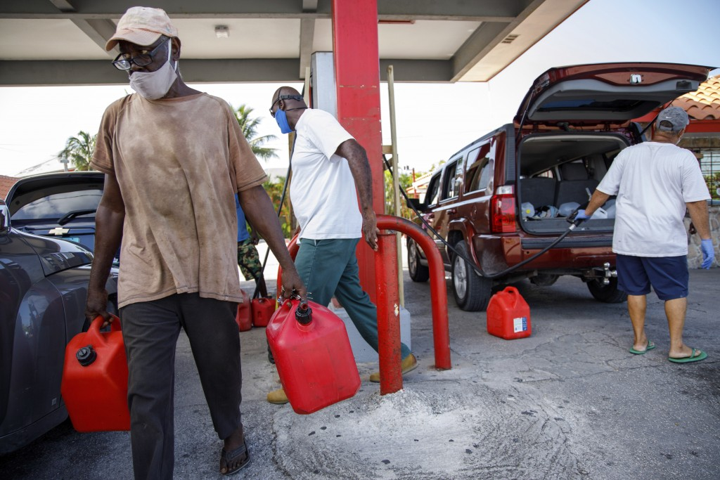 A resident walks with containers filled with gasoline at Cooper's gas station before the arrival of Hurricane Isaias in Freeport, Grand Bahama, Bahama...