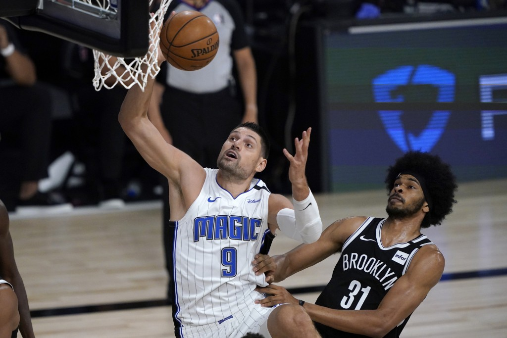 Orlando Magic's Nikola Vucevic (9) heads to the basket as Brooklyn Nets' Jarrett Allen (31) defends during the first half of an NBA basketball game Fr...