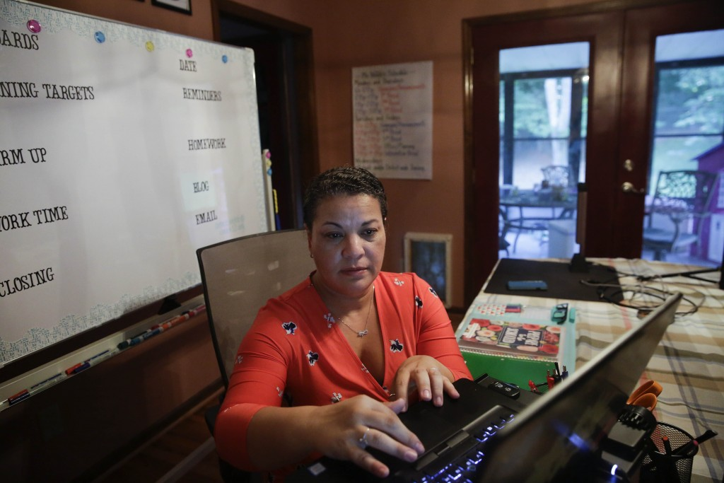 Aimee Rodriguez Webb works on her computer reading emails at her dinning room table that she set up as a virtual classroom for a Cobb County school, o...
