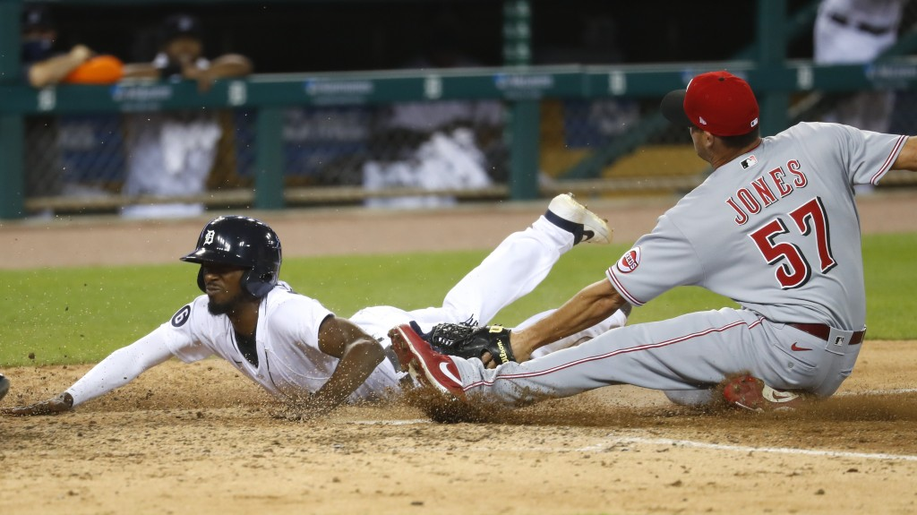 Detroit Tigers' Travis Demeritte beats the tag of Cincinnati Reds relief pitcher Nate Jones (57) to score at home plate on a wild pitch in the seventh...
