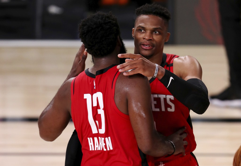 Houston Rockets Russell Westbrook, right, celebrates with James Harden (13) after defeating the Dallas Mavericks in an NBA basketball game Friday, Jul...