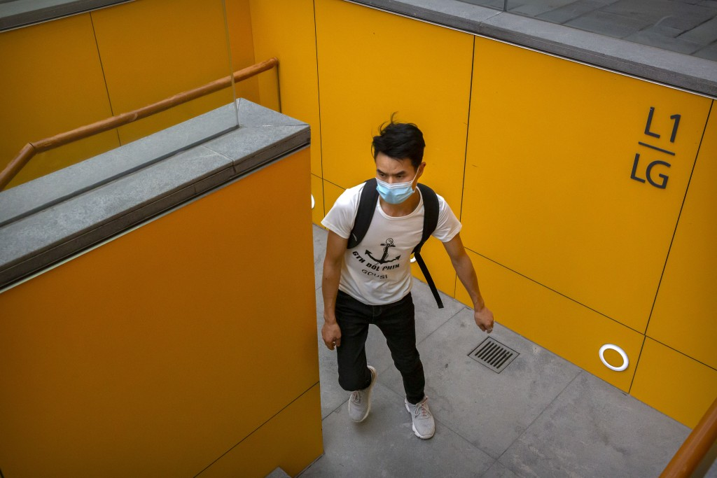 A man wearing a face mask to protect against the coronavirus walks up a staircase at an outdoor shopping area in Beijing, Saturday, Aug. 1, 2020. Chin...