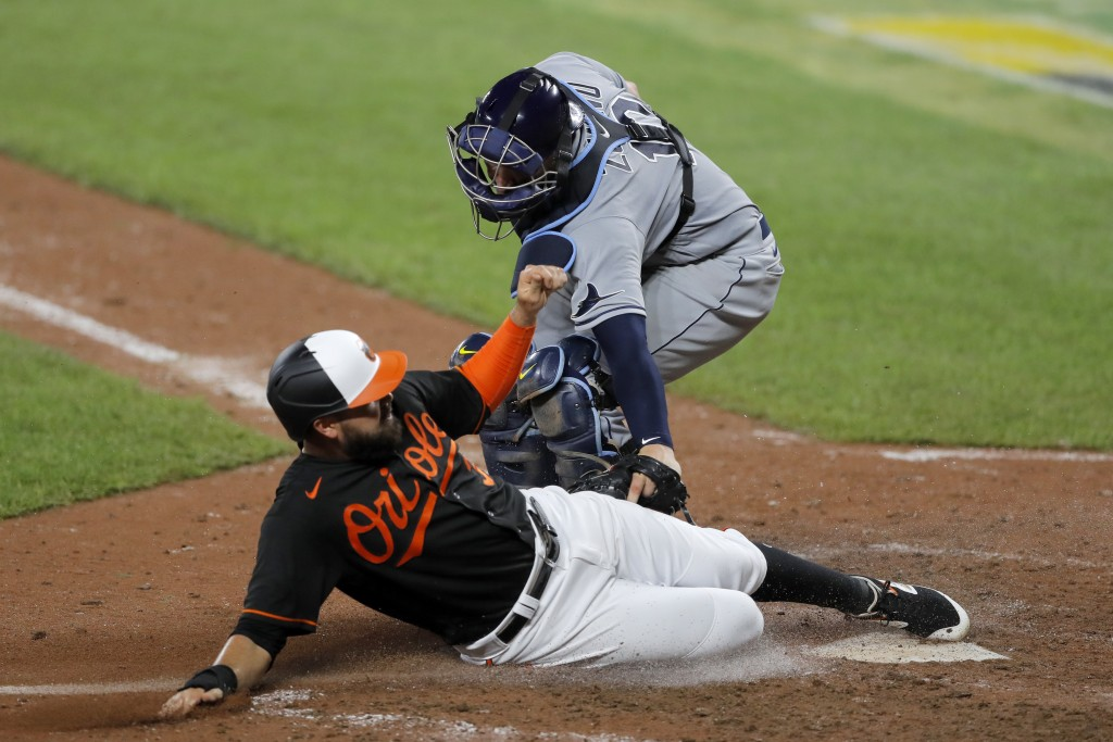 Baltimore Orioles' Renato Nunez, bottom, slides in under the tag of Tampa Bay Rays catcher Mike Zunino to score on a ball hit by Orioles' Rio Ruiz dur...