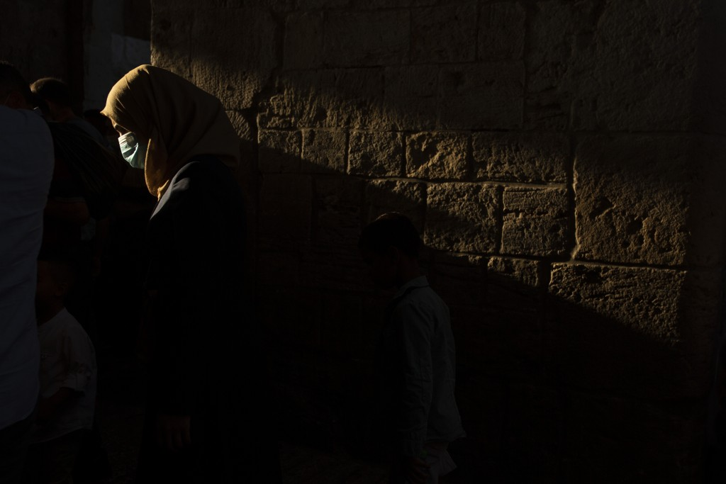 A woman wears a mask to help curb the spread of the coronavirus as she leaves prayers for Eid Al-Adha, or feast of sacrifice, in the Old City of Jerus...