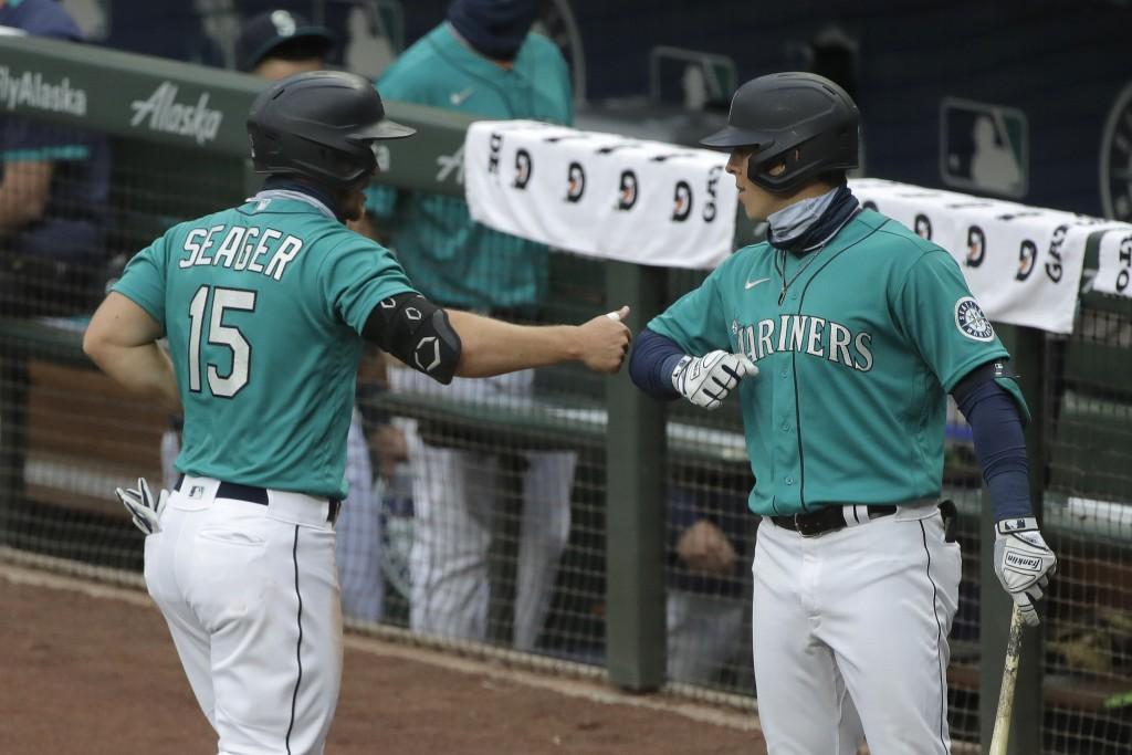 Seattle Mariners' Kyle Seager, left, greets Dylan Moore, right, after scoring against the Oakland Athletics during the fourth inning of a baseball gam...