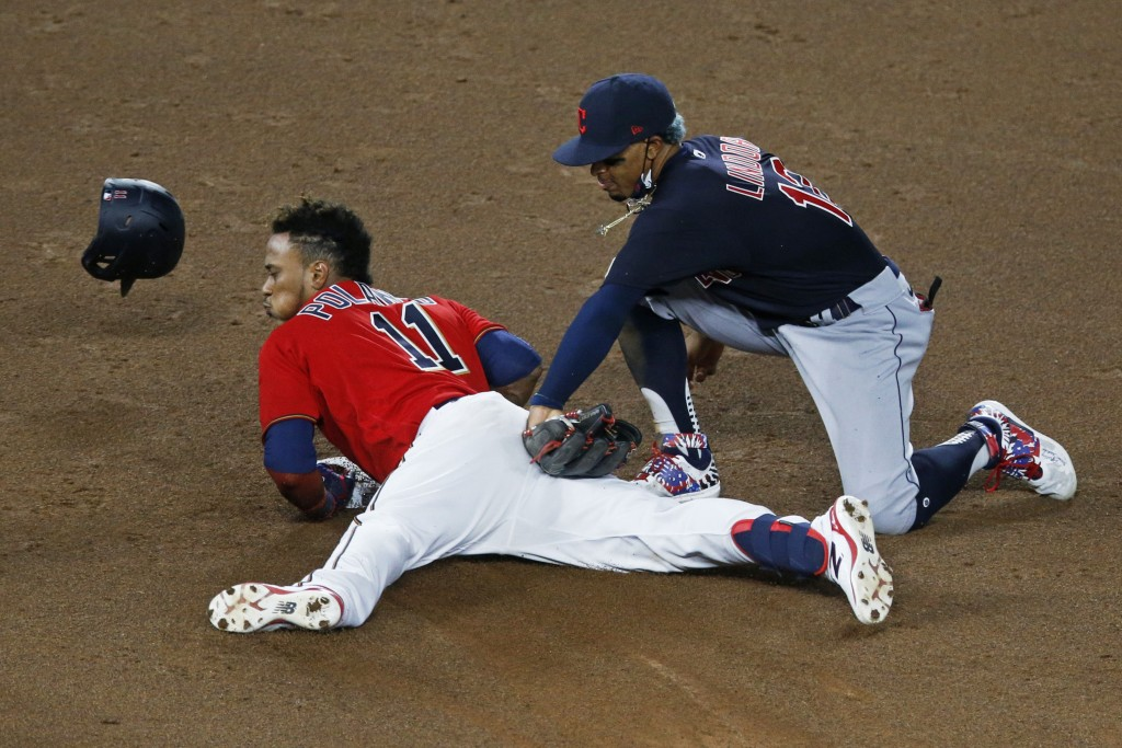 Minnesota Twins' Jorge Polanco, left, beats the tag by Cleveland Indians shortstop Francisco Lindor as he doubles in the fifth inning of a baseball ga...