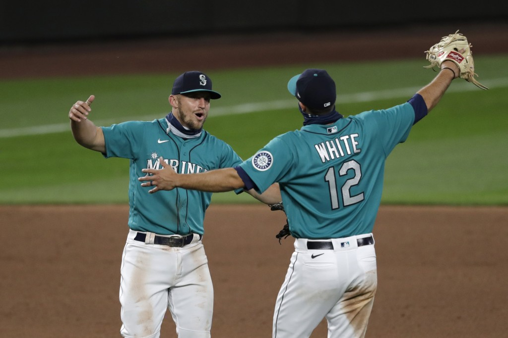 Seattle Mariners' Kyle Seager, left, and Evan White (12) keep their distance as they celebrate after the team beat the Oakland Athletics in a baseball...
