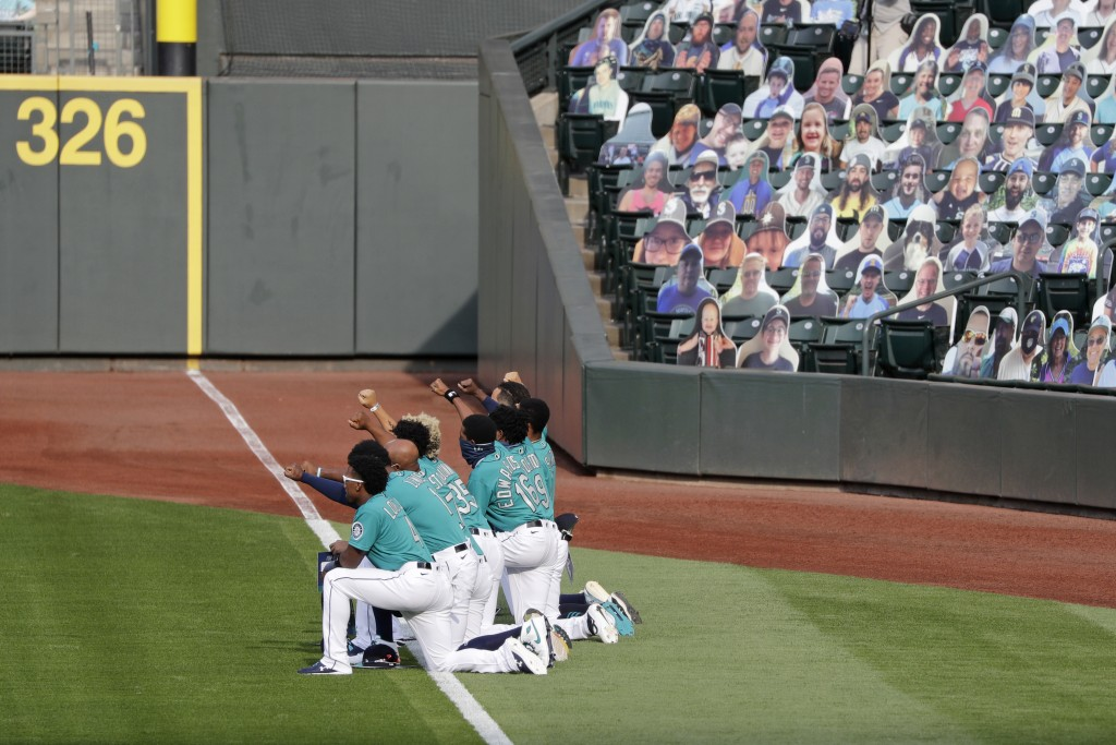 Seattle Mariners players kneel along the left field line with fists in the air as they watch a video tribute after the playing of the national anthem ...