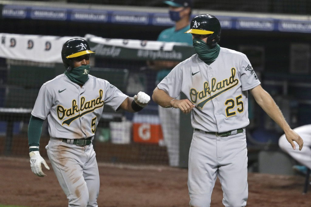 Oakland Athletics' Tony Kemp (5) and Stephen Piscotty (25) bump elbows in congratulations after both scored against the Seattle Mariners in the eighth...