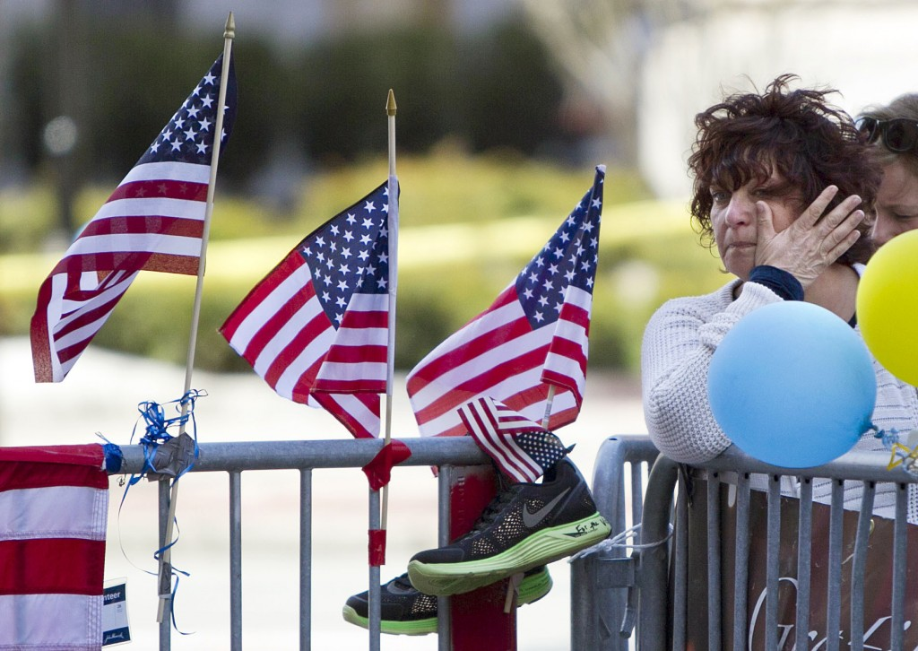 FILE - In this April 22, 2013 file photo, a woman wipes a tear at a memorial for the victims of the Boston Marathon bombing on Boylston Street near th...
