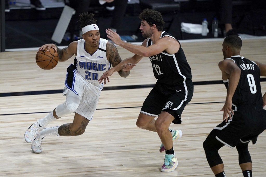 Orlando Magic's Markelle Fultz (20) heads to the basket as Brooklyn Nets' Joe Harris (12) and Timothe Luwawu-Cabarrot (9) defend during the first half...