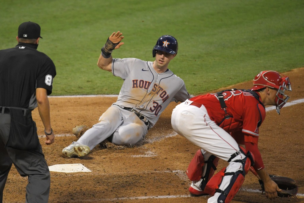 Houston Astros' Kyle Tucker, center, scores on a sacrifice fly by George Springer as Los Angeles Angels catcher Jason Castro, right, takes a late thro...