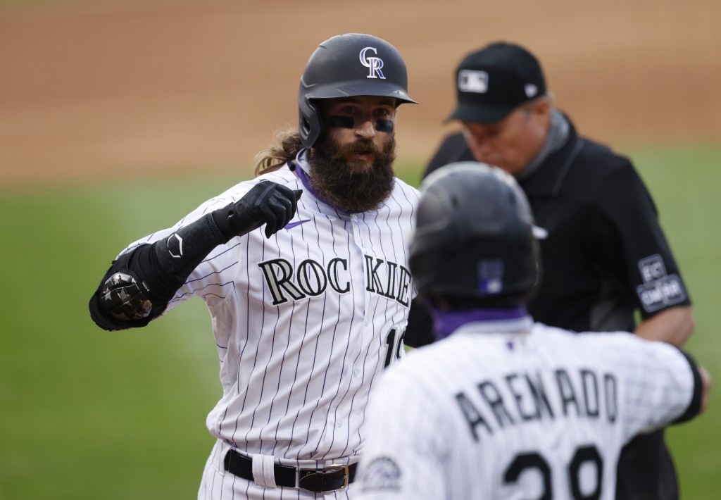 Colorado Rockies' Charlie Blackmon, back, is congratulated by Nolan Arenado as Blackmon crosses home plate after hitting a two-run home run off San Di...
