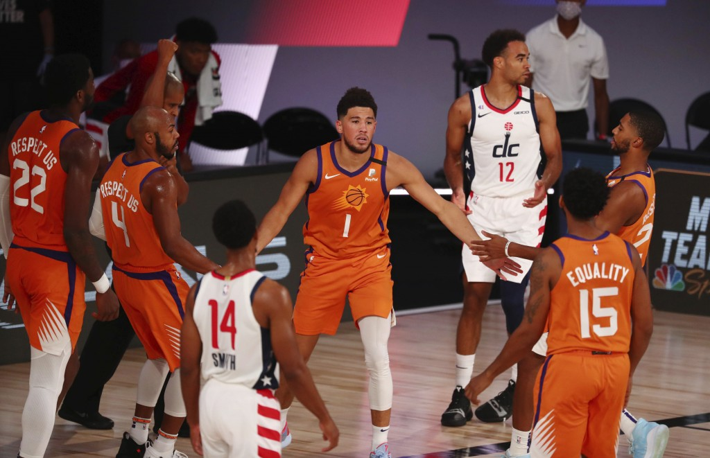Phoenix Suns guard Devin Booker (1) celebrates with teammates in the first half of an NBA basketball game against the Washington Wizards in Lake Buena...