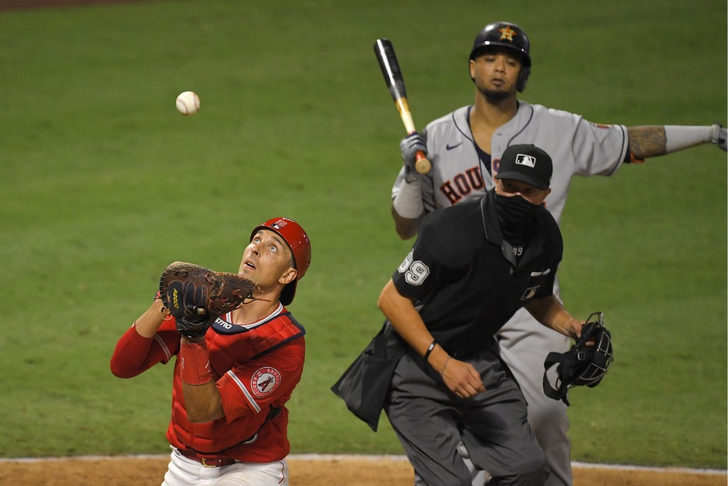 Los Angeles Angels catcher Jason Castro, left, catches a ball that was fouled off the ground by Houston Astros' Martin Maldonado, upper right, as home...