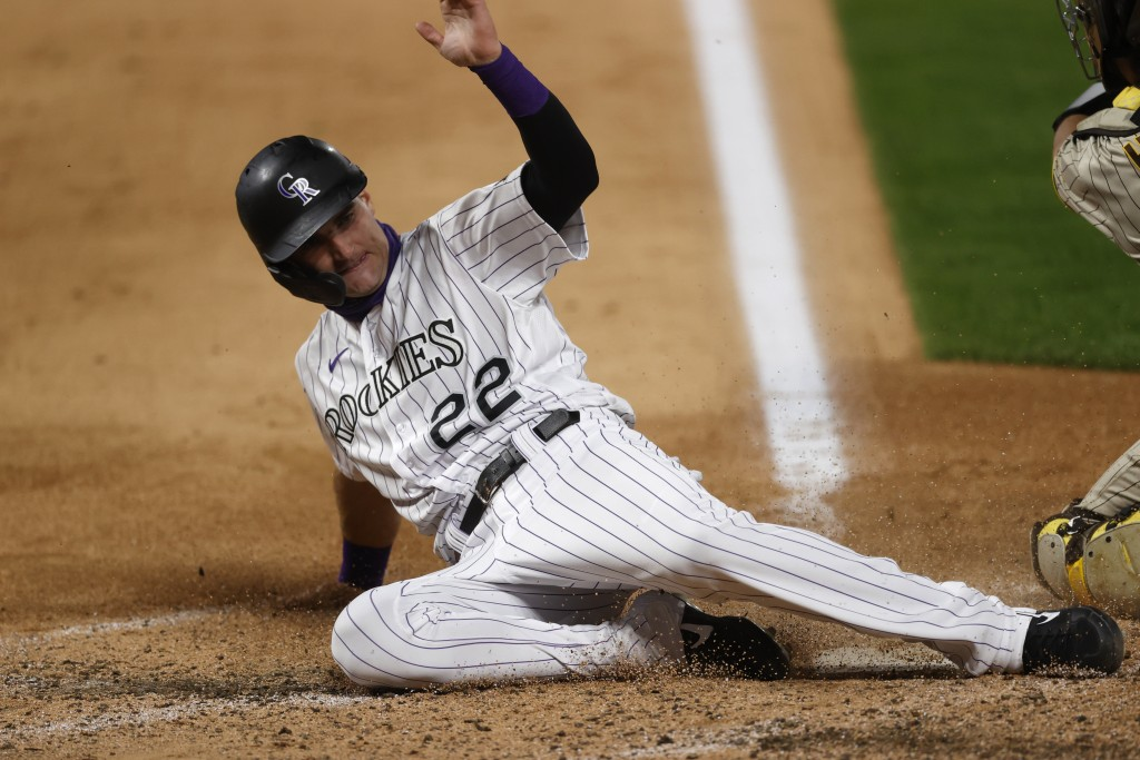 Colorado Rockies' Sam Hilliard, left, slides safely into home plate to score on a double hit by pinch hitter Matt Kemp as San Diego Padres catcher Aus...