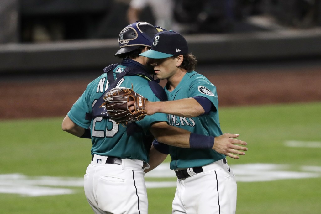 Seattle Mariners closing pitcher Taylor Williams, right, embraces catcher Austin Nola after the team beat the Oakland Athletics in a baseball game dur...