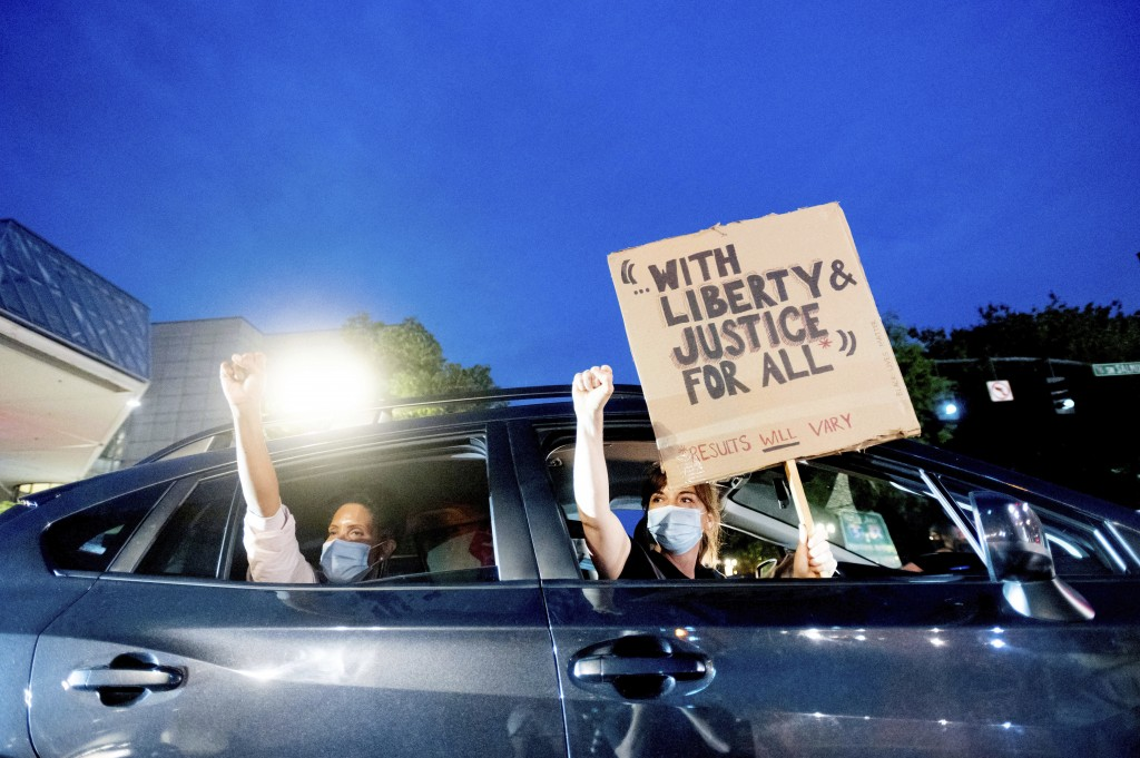 Bobbi Snethen, right, holds a sign during a protest caravan for Black Lives Matter on Friday, July 31, 2020, in Portland, Ore. Following an agreement ...