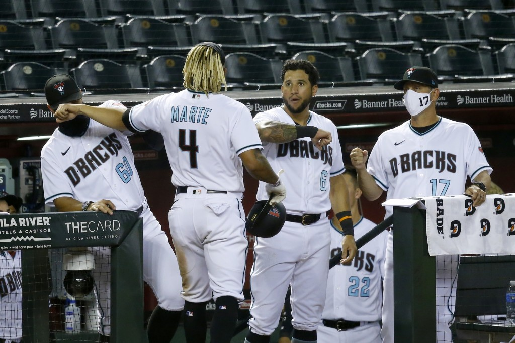 Arizona Diamondbacks' Ketel Marte (4) celebrates his run scored against the Los Angeles Dodgers with Diamondbacks bench coach Luis Urueta (60), David ...