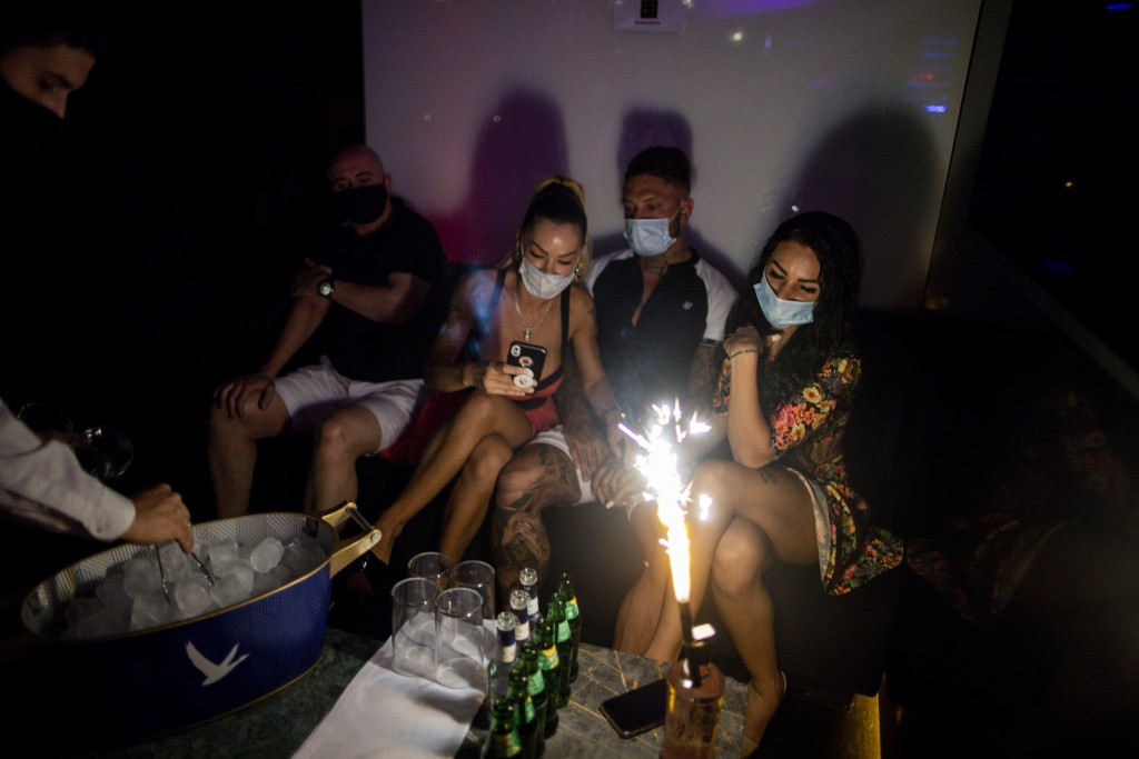 People wearing face masks to prevent the spread of coronavirus gather in a discotheque in Madrid, Spain, early Saturday, July 25, 2020. Nightlife is b...