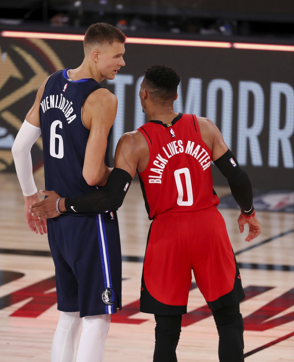 Houston Rockets Russell Westbrook (0) talks with Dallas Mavericks Kristaps Porzingis (6) after an NBA basketball game Friday, July 31, 2020, in Lake B...