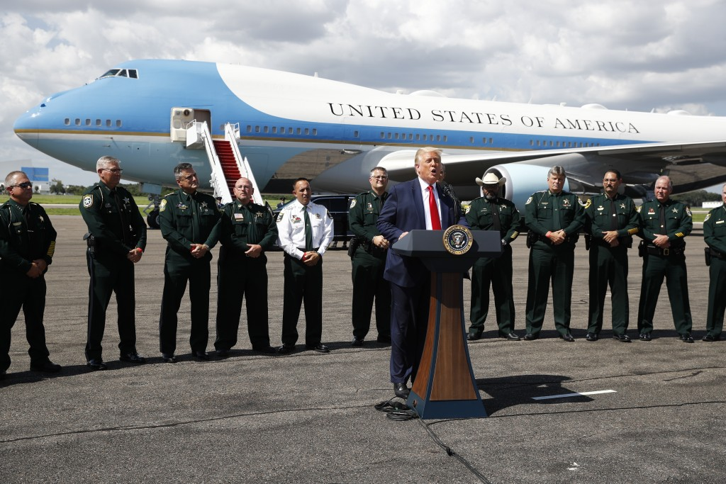 With Air Force One in the background, President Donald Trump speaks during a campaign event with Florida Sheriffs in Tampa, Fla., Friday, July 31, 202...