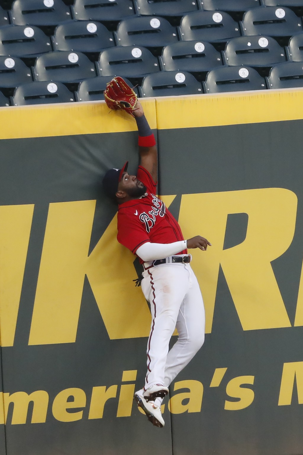 Atlanta Braves left fielder Marcell Ozuna goes up the wall as he tries to catch a ball hit for a two-run home run by New York Mets' J.D. Davis in the ...