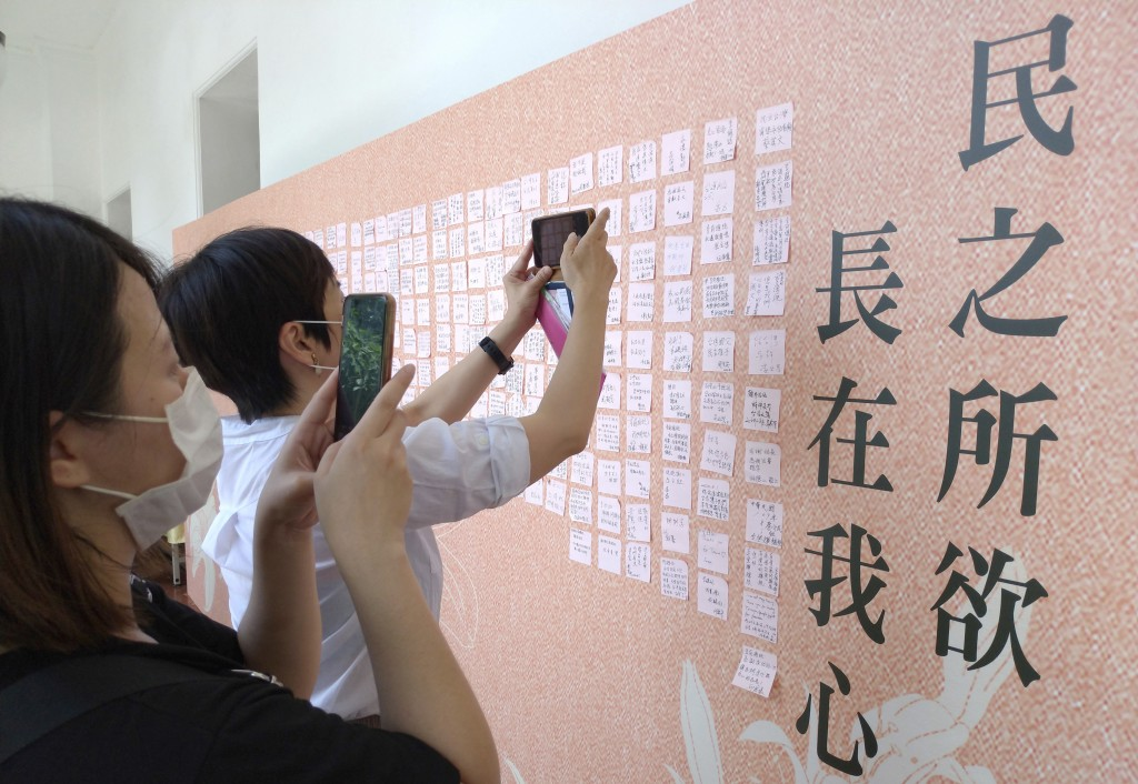 People take photos of a message wall to the late former President Lee Teng-hui with Lee's quote ''The desire of the people is in my heart'' at the mem...