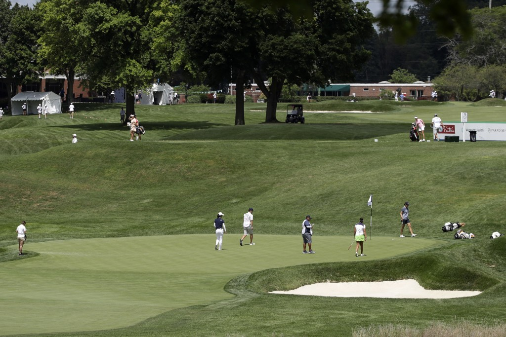 A group putts on the 17th green, below, during the first round of the LPGA Drive On Championship golf tournament at Inverness Golf Club in Toledo, Ohi...