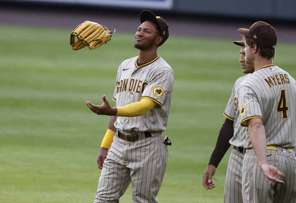 San Diego Padres left fielder Edward Olivares, left, tosses his glove in the air while chatting with center fielder Trent Grisham, center, and San Die...