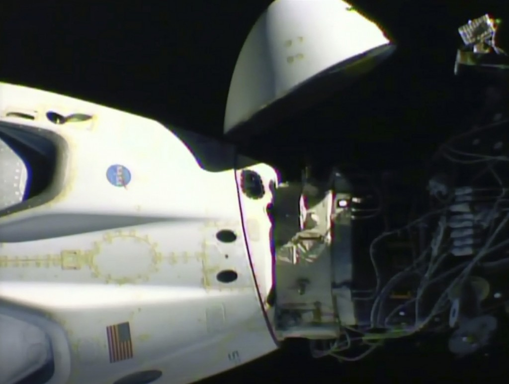 This image from video made available by NASA shows the SpaceX Crew Dragon capsule, left, before it undocks from the International Space Station on Sat...