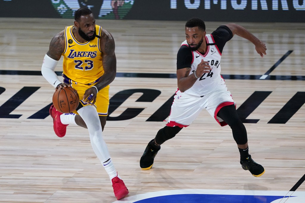 Los Angeles Lakers' LeBron James (23) drives into Toronto Raptors' Norman Powell (24) during the first half of an NBA basketball game Saturday, Aug. 1...