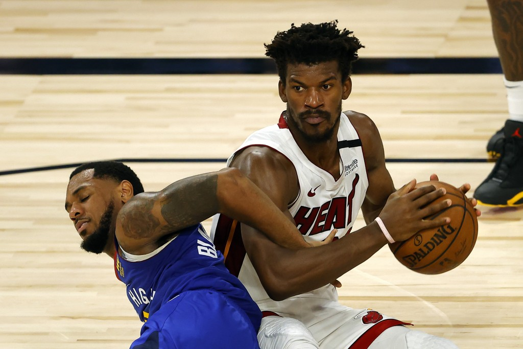 Denver Nuggets' Monte Morris tangles for the ball against Miami Heat's Jimmy Butler during an NBA basketball game, Saturday, Aug. 1, 2020, in Lake Bue...