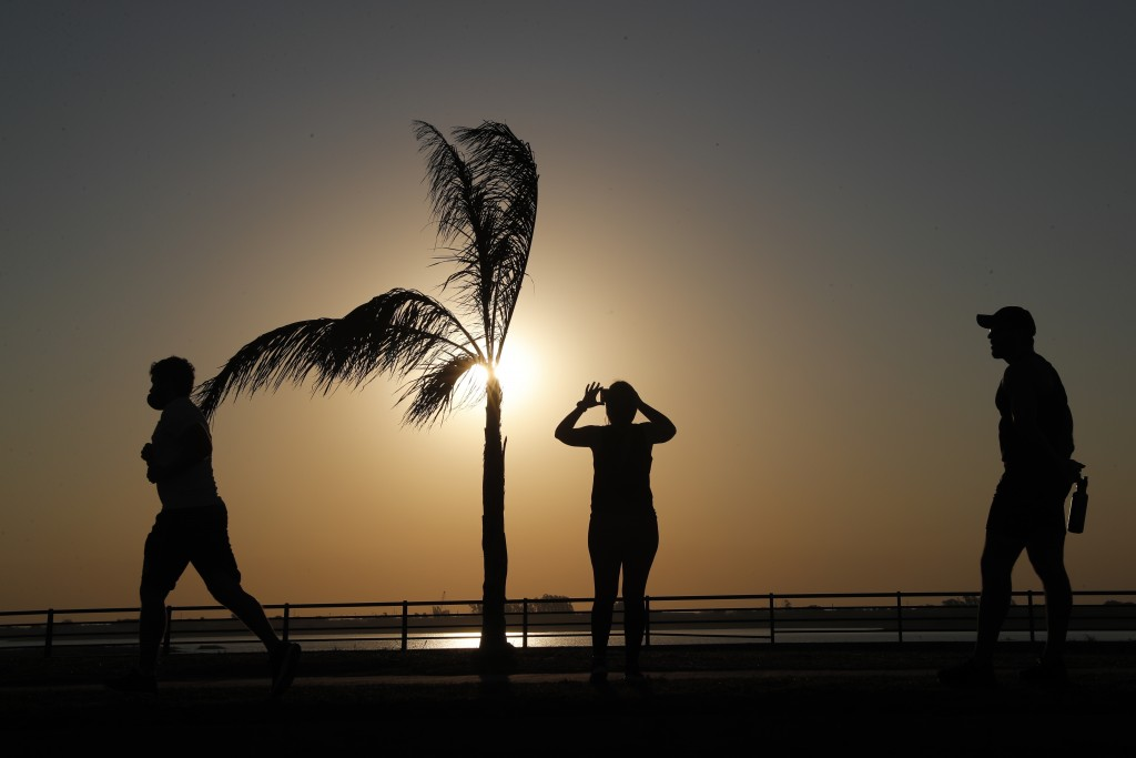People are silhouetted against the sky with a setting sun in Asuncion, Paraguay, Saturday, Aug. 1, 2020, amid the new coronavirus pandemic. (AP Photo/...