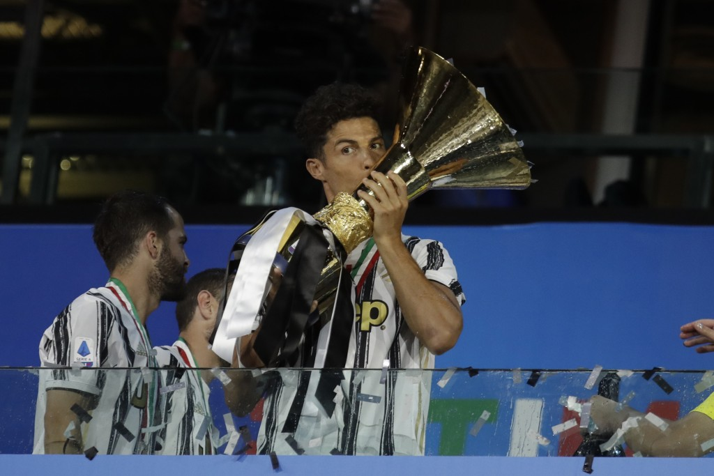 Juventus' Cristiano Ronaldo kisses the trophy as Juventus players celebrate winning an unprecedented ninth consecutive Italian Serie A soccer title, a...