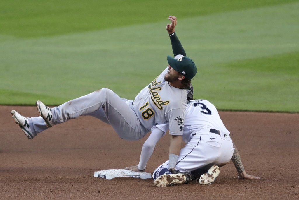 Oakland Athletics second baseman Chad Pinder (18) falls onyo Seattle Mariners' J.P. Crawford after tagging Crawford out at second base on a stolen-bas...