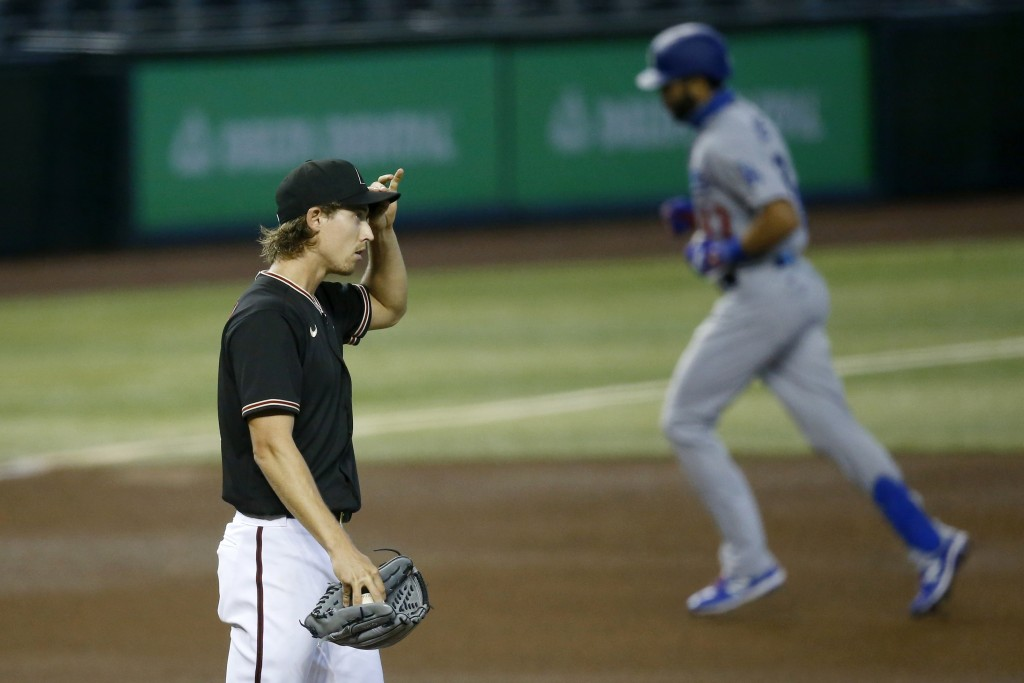 Arizona Diamondbacks starting pitcher Luke Weaver, left, pauses on the mound after giving up a two-run home run to Los Angeles Dodgers' Edwin Rios, ri...
