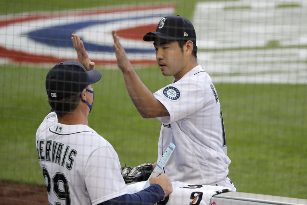 Seattle Mariners starting pitcher Yusei Kikuchi, right, greets manager Scott Servais while heading into the dugout after the top of the sixth inning o...