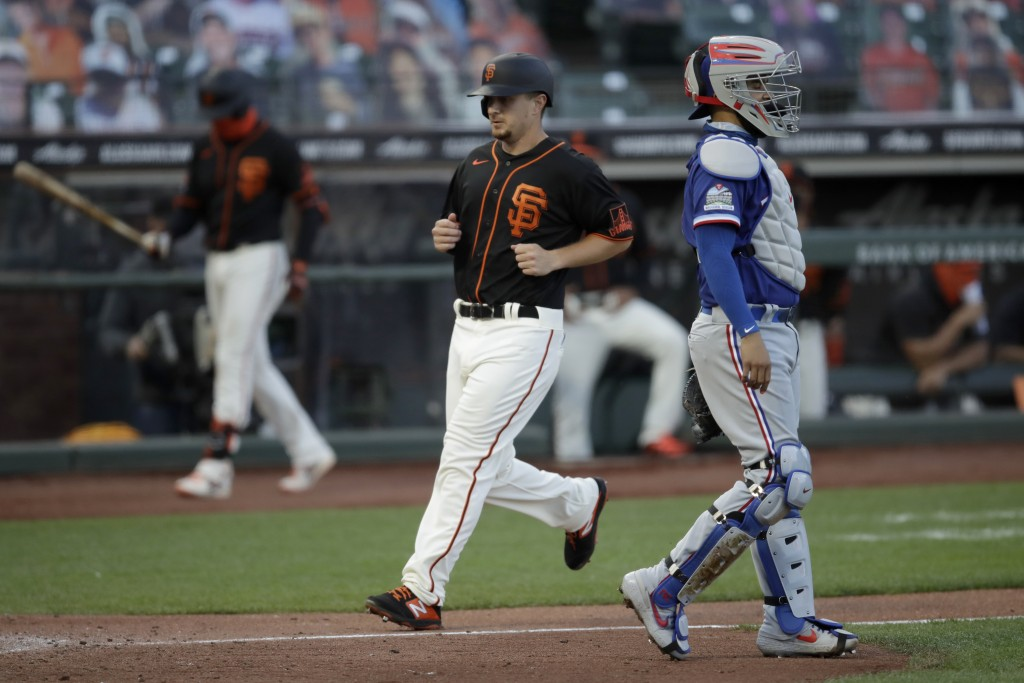 San Francisco Giants' Alex Dickerson, center, scores past Texas Rangers catcher Robinson Chirinos during the third inning of a baseball game Saturday,...