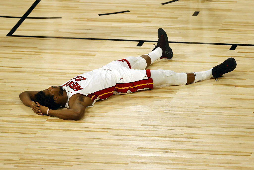 Miami Heat's Jimmy Butler lays on the court after drawing a foul against the Denver Nuggets during the first half of an NBA basketball game, Saturday,...