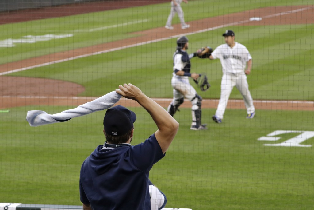 A Seattle Mariner waves a towel in celebration as starting pitcher Yusei Kikuchi, right, greets catcher Austin Nola as they head off the field after t...