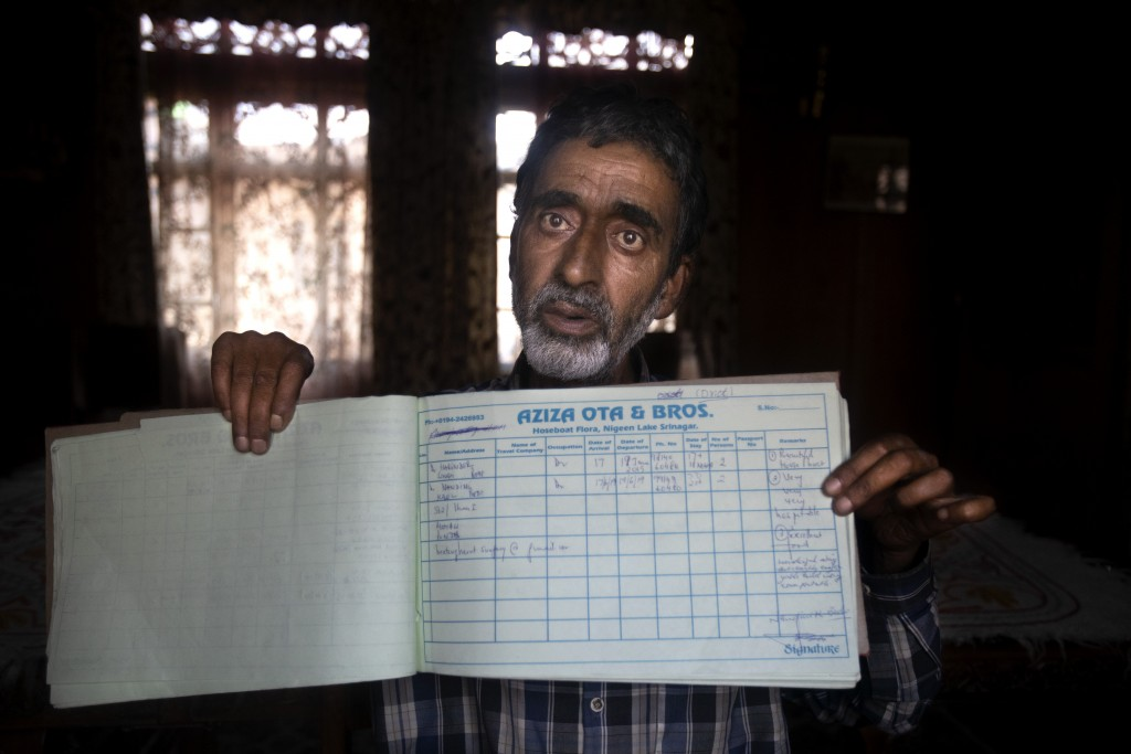 A Kashmiri houseboat owner Ghulam Qadir shows his guest entry book which was last filled in July 2019, in Srinagar, Indian controlled Kashmir,Tuesday,...