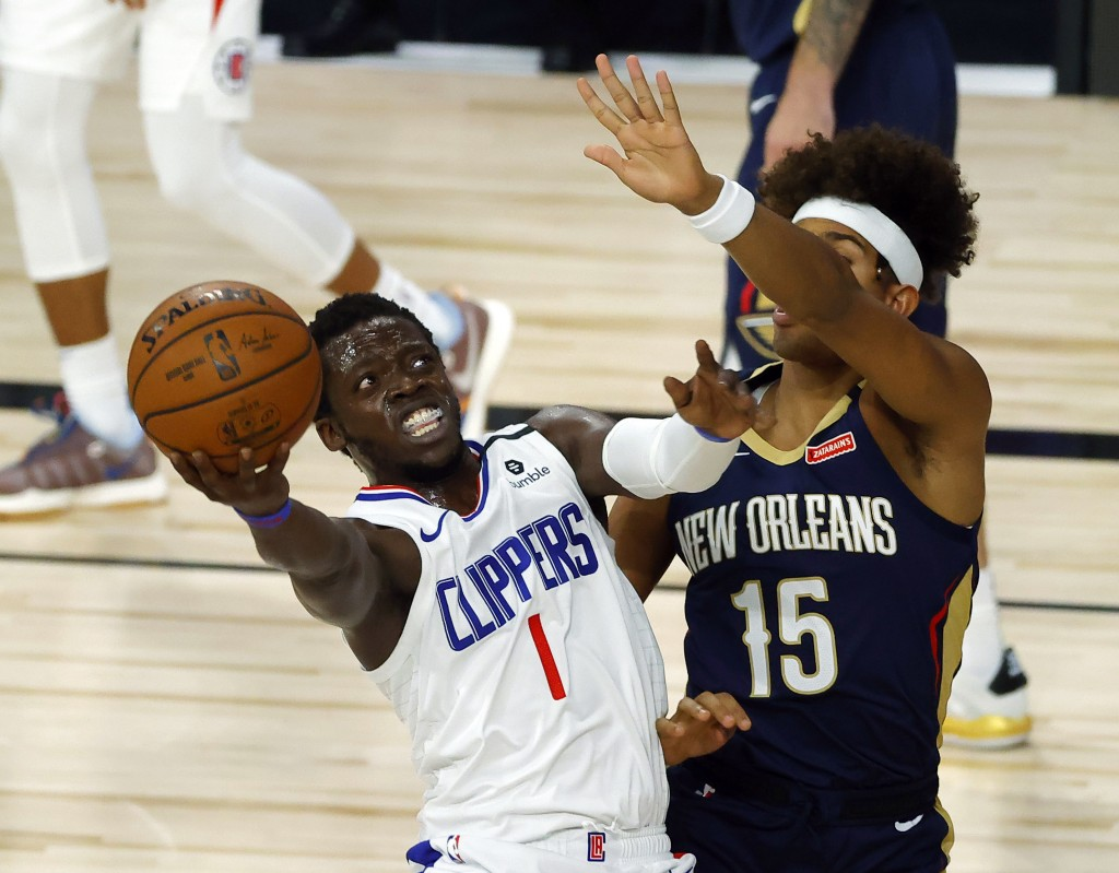 Los Angeles Clippers' Reggie Jackson (1) shoots against New Orleans Pelicans' Frank Jackson (15) during an NBA basketball game Saturday, Aug. 1, 2020,...