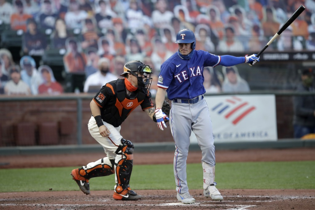 San Francisco Giants catcher Tyler Heineman, left, tags out his brother Texas Rangers' Scott Heineman after a foul tip during the second inning of a b...