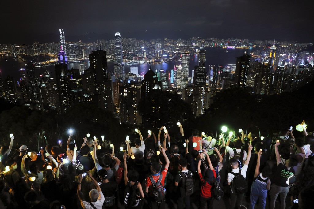 FILE - In this Friday, Sept. 13, 2019 file photo, demonstrators hold up the mobile phone lights as they form a human chain at the Peak, a tourist spot...