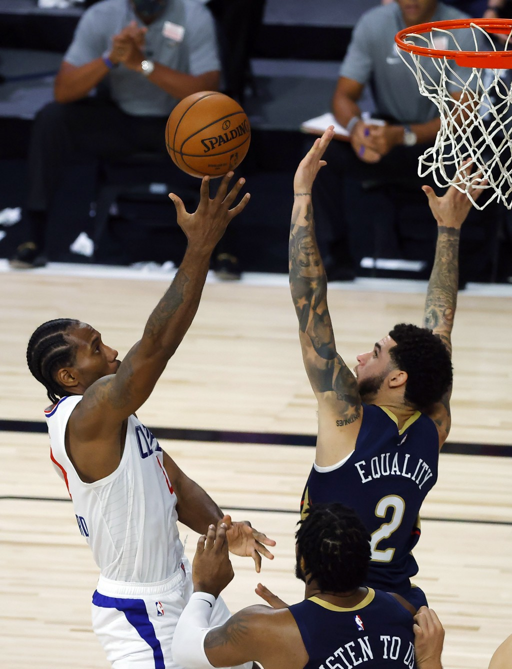 Los Angeles Clippers' Kawhi Leonard, left, goes up against New Orleans Pelicans' Lonzo Ball, top right, during an NBA basketball game Saturday, Aug. 1...