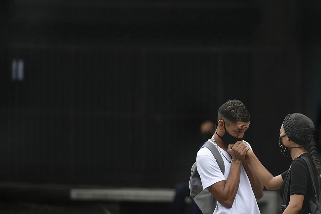 A man, wearing a protective face mask, kisses his girlfriend's hand on Sabana Grande boulevard in Caracas, Venezuela, Saturday, Aug. 1, 2020, amid the...